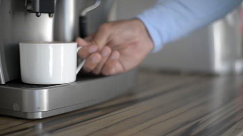 Taking Full Cup of Coffee from Coffee Maker
