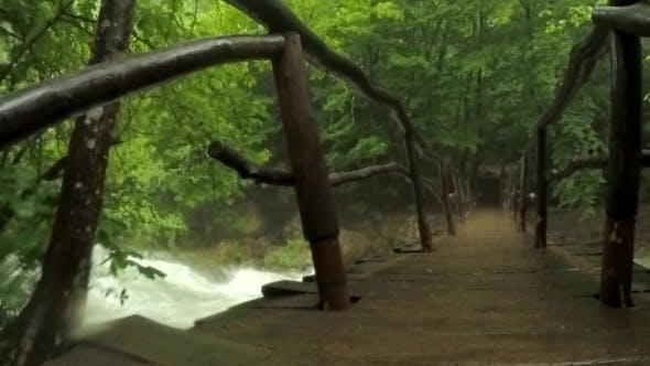 Thumbnail for Hooded Tourist Walking On Bridge Hanging Above