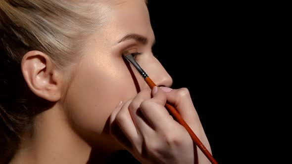 Thumbnail for Professional Face Makeup for Photo Shooting. Artist Applying Eyeshadows. Black. Closeup