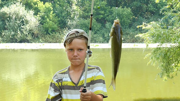 Cover Image for Young Caucasian Boy With Fishing Pole And Fish