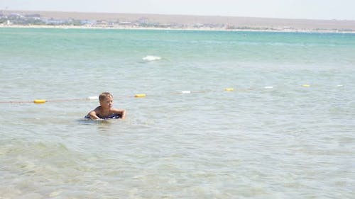 Happy Child Learns to Swim in the Sea on an Inflatable Pillow