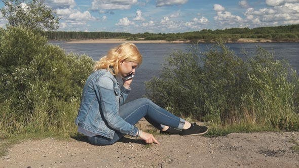 Cover Image for Girl Speaks on the Phone Near the River