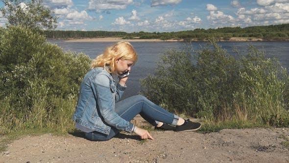 Thumbnail for Girl Speaks on the Phone Near the River