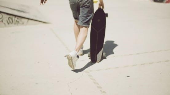 Thumbnail for Mann zu Fuß bei einem skate park mit seinem skateboard