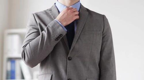 Close Up Of Man In Suit Adjusting Necktie 1