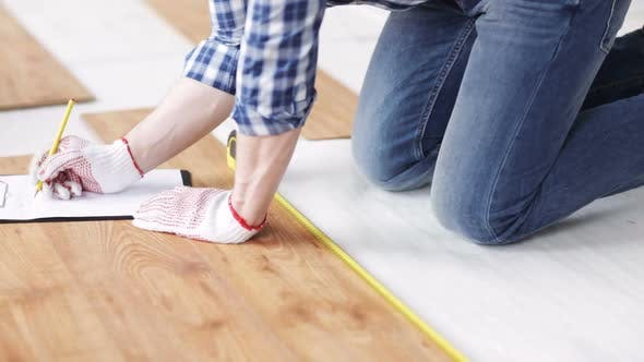 Thumbnail for Close Up Of Man Measuring Flooring And Writing 2