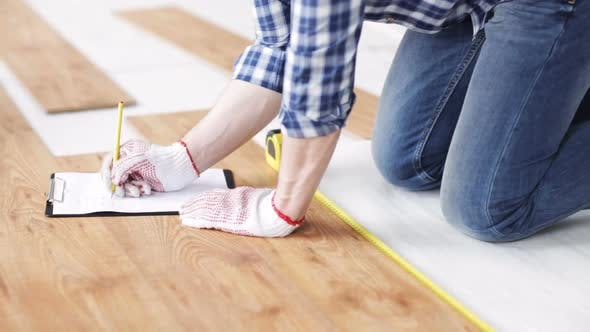 Thumbnail for Close Up Of Man Measuring Flooring And Writing 3