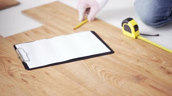 Thumbnail for Close Up Of Man Measuring Flooring And Writing 5