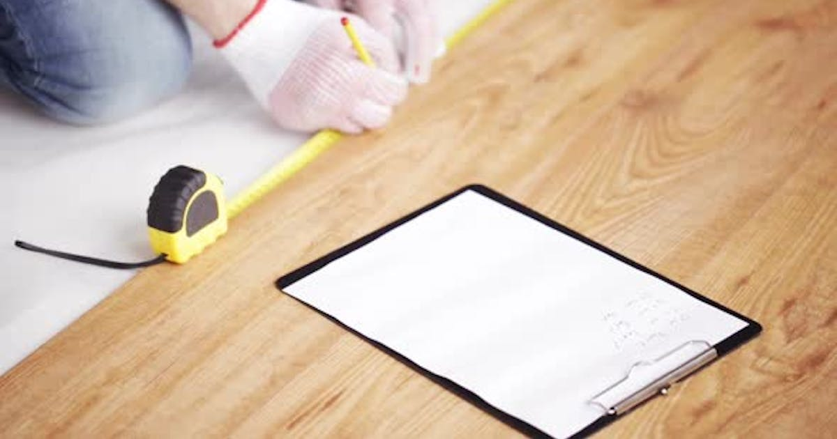 Close Up Of Man Measuring Flooring And Writing 7