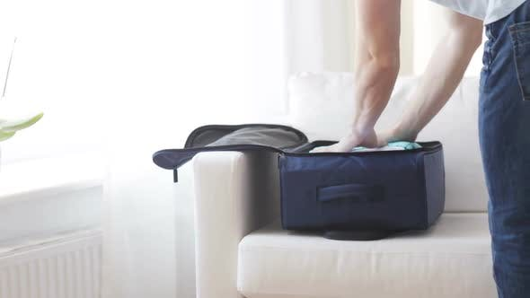 Thumbnail for Close Up Of Man Packing Clothes Into Travel Bag