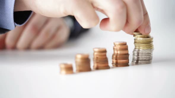 Thumbnail for Close Up Of Businessman Putting Coins Into Columns 7