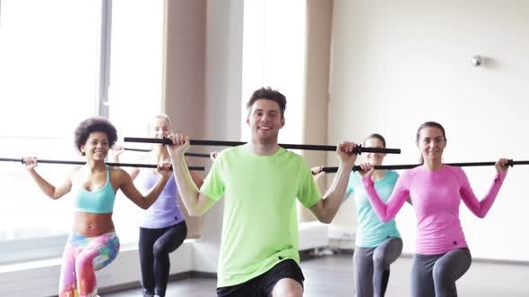 Cover Image for Group Of People Exercising With Bars In Gym 2