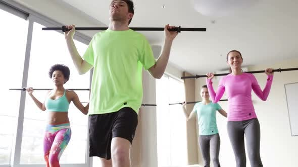Cover Image for Group Of People Exercising With Bars In Gym 5