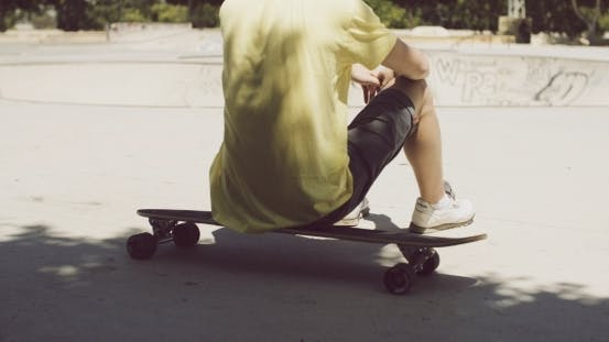 Thumbnail for Man Sitting On His Longboard At a Skate Park