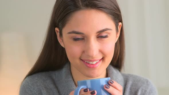 Happy woman with a mug of hot coffee