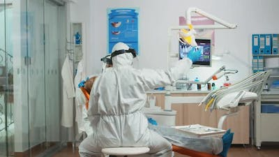 Dentist and Assistant in Coverall Examining Mouth of Patient