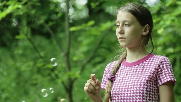 Thumbnail for Young Girl Catches Soap Bubbles In The Park