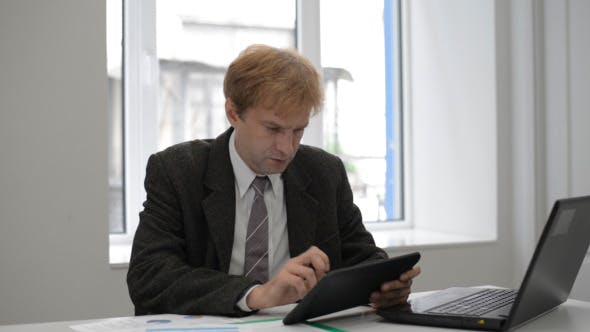 Cover Image for Businessman Typing on Tablet