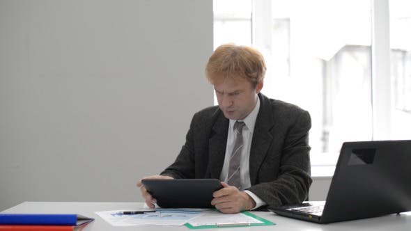 Cover Image for Anxious Businessman Using Tablet at Work