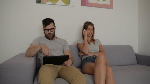 Thumbnail for Man Using Tablet, Girl Talking on Smartphone