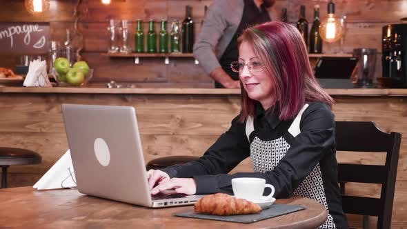 Woman Types on Laptop in Vintage Pub or Coffee Shop