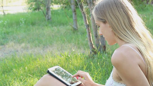 Thumbnail for Beautiful Girl Using Tablet in the Park