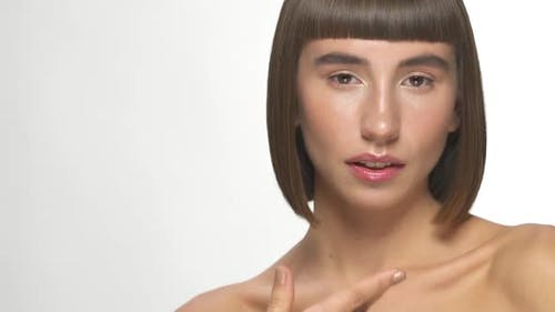 Pretty Woman with Short Hairstyle Pointing on Face and Shows Good Gesture