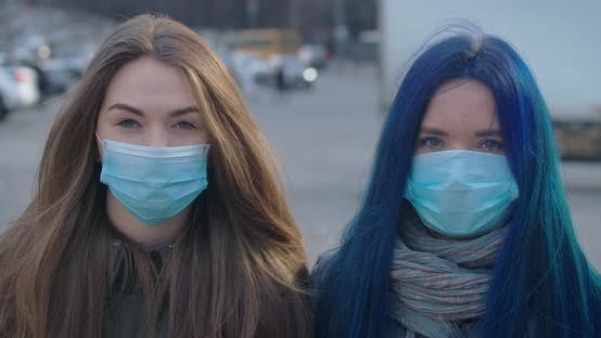 Thumbnail for Close-up Faces of Two Young Women in Protective Masks Looking at Camera at the Background of Busy