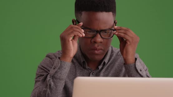 Cover Image for African American male putting on eye glasses to use computer on green screen