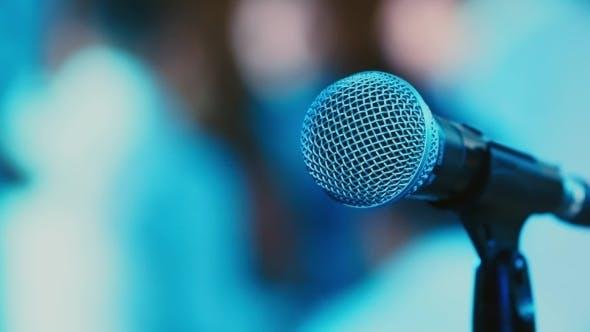 Mikrofon auf dem Hintergrund der tanzenden Menschen