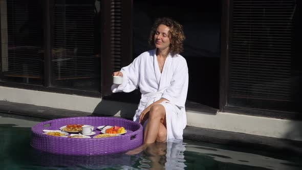 The Young Curly Caucasian Woman Starts Her Day with a Coffee and Breakfast From the Floating Tray at