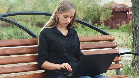Thumbnail for Young Girl Resting in a Park and Using Laptop