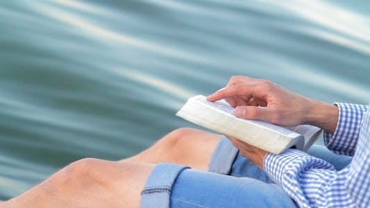 Thumbnail for Man Reading A Book On A Background Of The River