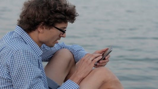 Thumbnail for Man Uses The Phone On The Background Of The River