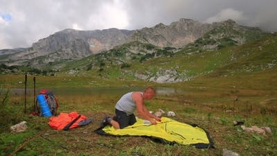 Male Tourist Sets Tourist Tent In The Mountains