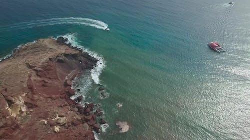 Boats near Red Beach on Santorini Island in Greece - drone view