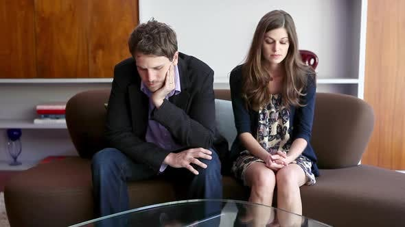 Thumbnail for Couple sitting on sofa arguing
