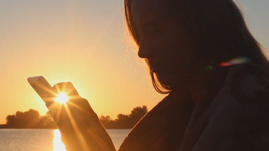 Thumbnail for Girl on the Beach at Sunrise Using a Tablet
