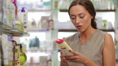 Beautiful Young Woman Looking For Proper Shampoo