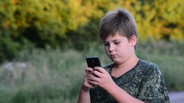 Thumbnail for Teenage Boy Uses  Smartphone  In The Open Air