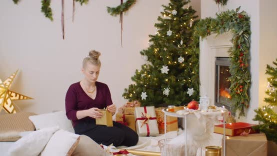 Thumbnail for Woman Wrapping Christmas Present By Fireplace At Home