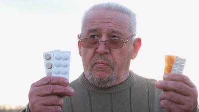 Gray Sick Grandfather with Pills in His Hands