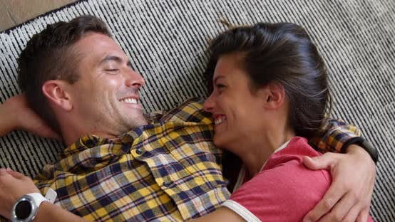 Cute couple relaxing together on floor mat in living room at home