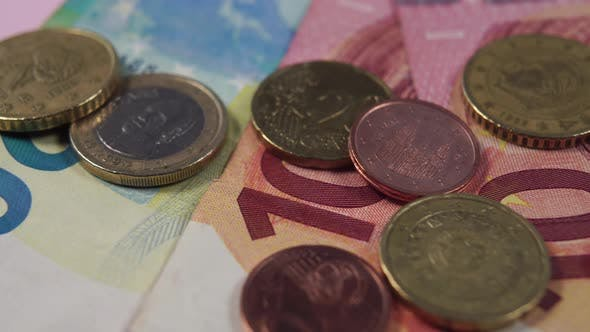 Euro banknotes and coins close-up on a pink background.
