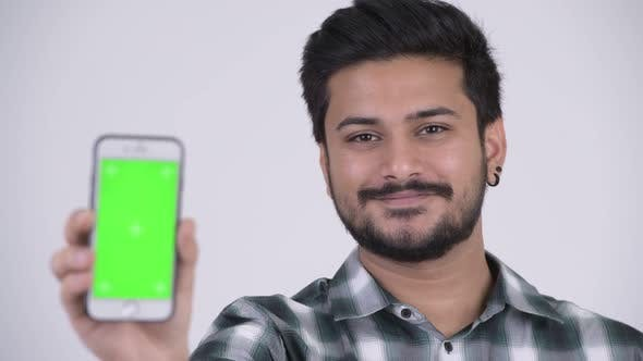 Thumbnail for Young Happy Bearded Indian Man Smiling While Showing Phone