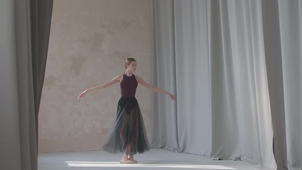 Fragile Young Ballerina Against the Background of Long Light Curtains Raises Her Legs High
