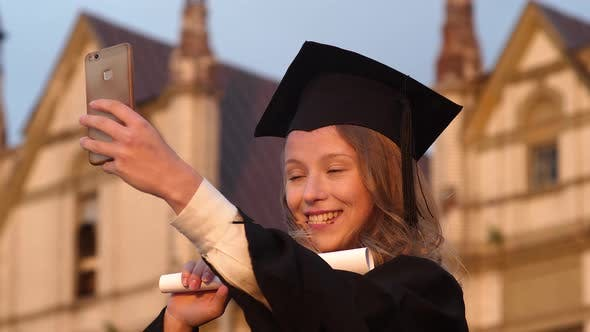 Thumbnail for Attractive Graduate Girl Taking Selfie on Graduation Day Holding Diploma