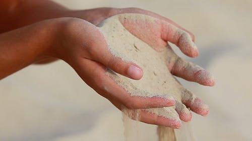 Streuen Sand durch Finger