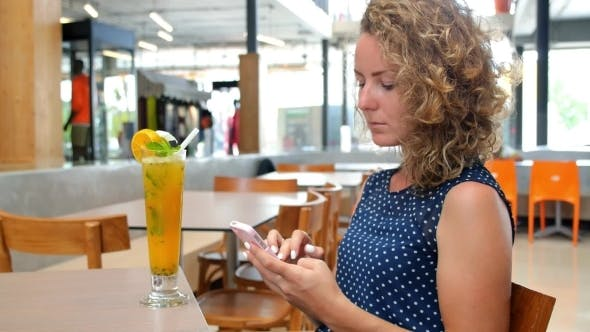 Thumbnail for Young Woman Using Smart Phone In Cafe