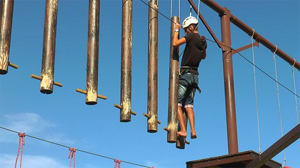 Man Goes on Beam that are Hanging on the Ropes